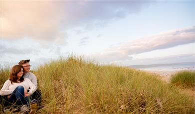 Couple sitting in Kinmel Dunes with sea in background