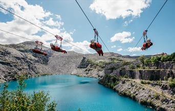 Four riders on Velocity zip wire over Penrhyn Quarry lake