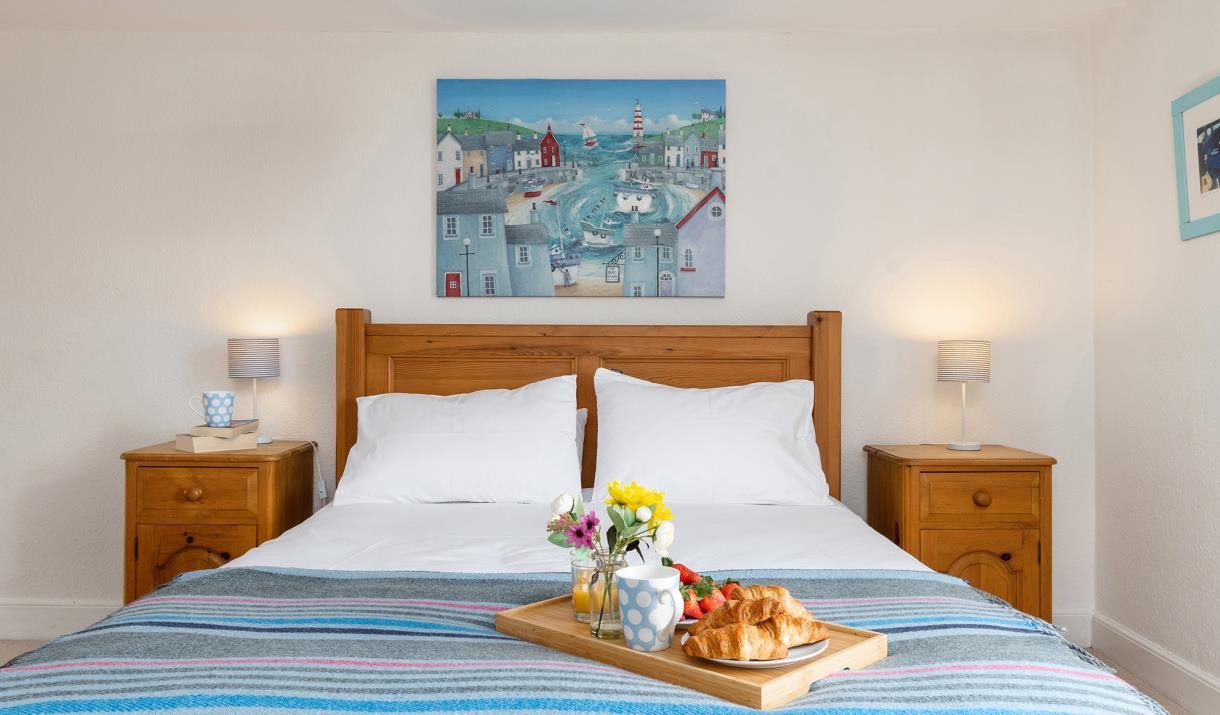 Double bedroom with breakfast tray on bed featuring flowers and croissants.