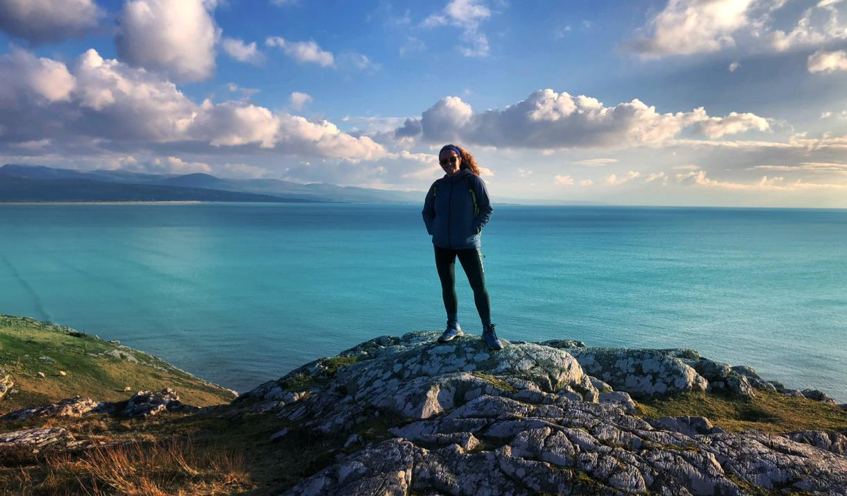 Sian Humpherson standing on mountain with sea in background