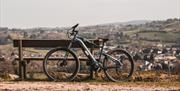 Image of a bike resting against a bench with a view over the mountain in the background