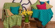Image of Trefriw Woollen Mills blankets and cushions on a chair and furniture.