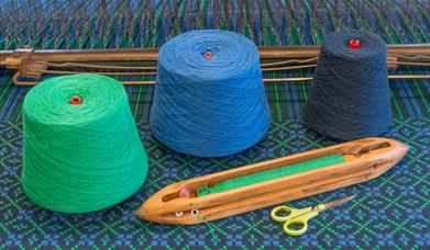 Image of green, blue and grey wool next to tools.