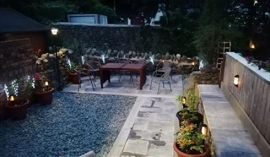 Garden area with gravelled and slabbed area with seating area and solar lighting.