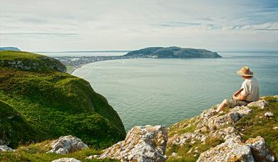 Man sat on top of Little Orme looking over to the Great Orme