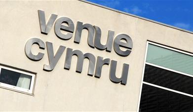Delwedd yn dangos logo Venue Cymru ar ochr yr adeilad
