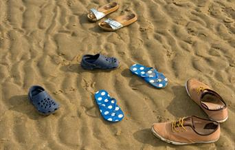 Assortment of shoes on the beach