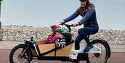 Image of woman and 2 children on a bike