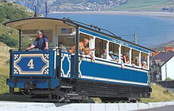 The Llandudno tram climbing up the Great Orme with Llandudno Bay in the background.