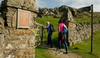 Two walkers at the gateway entry to Pensychnant Nature Reserve