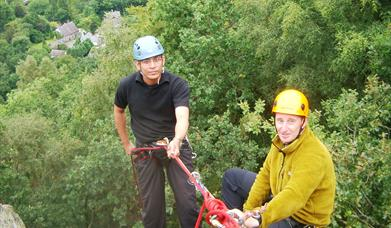 Two men preparing to abseil down rocks into the woods