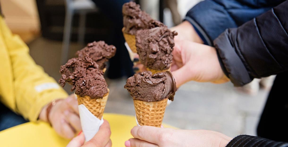 Three people holding chocolate gelato cones