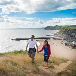 Couple on a romantic break walking the coast path at West Bay