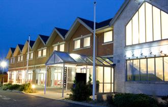 Front elevation and entrance of Hotel at dusk with internal lights switched on