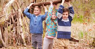 3 young children carrying a large wooden log to make a camp.