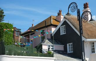 Quaint pink cottage behind iconic thatched cottages on seafront with garden overlooking Lyme Bay.