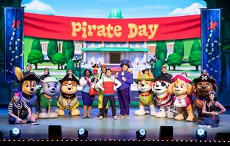 PAW Patrol Live! people dressed up as paw patrol dogs with other actors on stage below the banner 'Pirate Day'