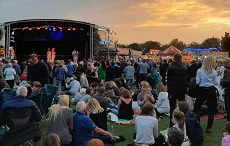ABBA tribute act playing on a stage in a park. Sunset behind and crowds in front enjoying the music