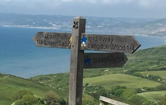 Wooden signpost for walking and cycling routes in Dorset