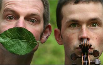 Two young men stand together, one has a leaf over his mouth, the other is holding a fiddle up to his face