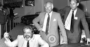 Old photo of John Haynes at Haynes International Motor Museum stood next to car on display