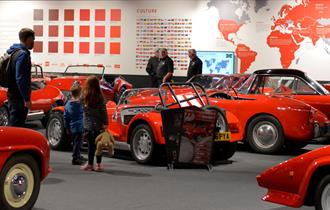 Visitors in the Red Room looking at the red cars