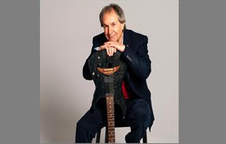 Musician Chris De Burgh sat facing camera with hands resting on an upsidedown guitar