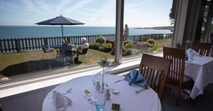 Dine at the Pines in the dining room or on the terrace with panoramic seaviews across the lawn.
