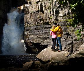couple at high force waterfall