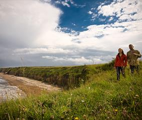 couple walking at Nose's Point on the Durham Heritage Coast