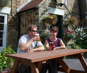 couple enjoying a drink outside a countryside pub.