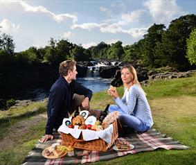 couple enjoying a picnic at Low Force Waterfall.
