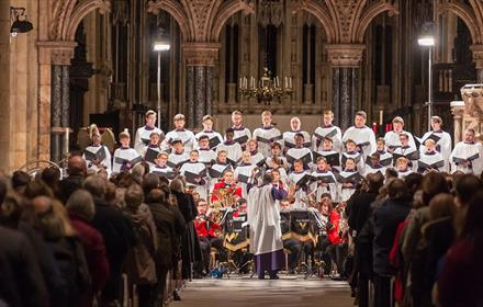 A concert in Durham Cathedral, with performers on stage and a full audience