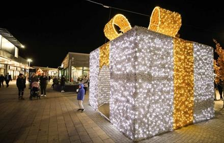 Giant Christmas present covered in white fairy lights with gold fairy lights for the ribbon