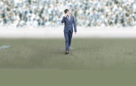man in suit walking on football pitch, crowd in background