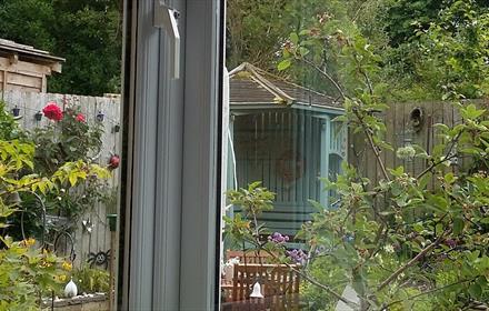 image of garden through a window, trees, roses, summer house, bird box