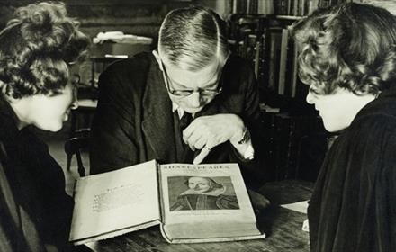 Three people looking at Shakespeare's manuscript at Palace Green Library