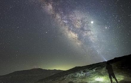 The image shows the silhouette of a man photographing The Milky Way galaxy from the hillside