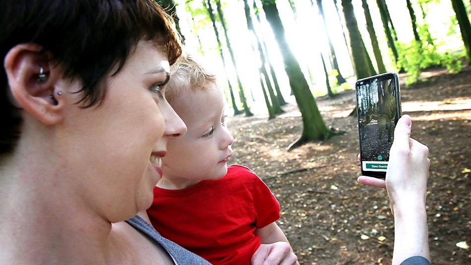 Woman with child looking at App on a mobile phone, forest setting