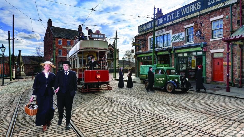 Beamish Museum 1900s Town. 2 People in Victorian Clothes Standing in the Cobbled Streets In front of a Tram.