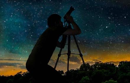 Silhouette of photographer gazing through a telescope at the night sky
