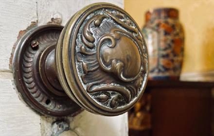close up of brass door knob on white door, slightly ajar