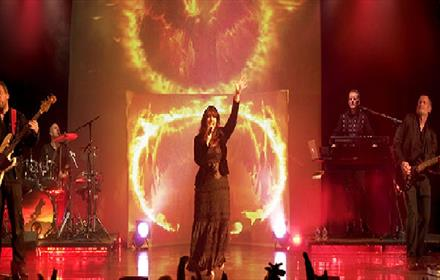 Cloudbusting - photo of the band on stage in front of a background of fire images