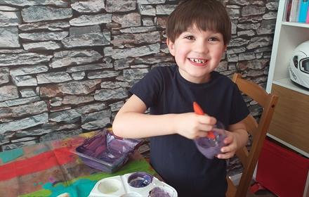 Boy mixing paint with painting on table