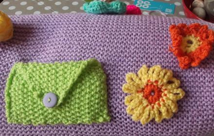 Example of knitting, purple with a green pocket and orange and yellow flowers