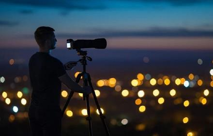 Photographer looking through telescope at the night sky above city lights