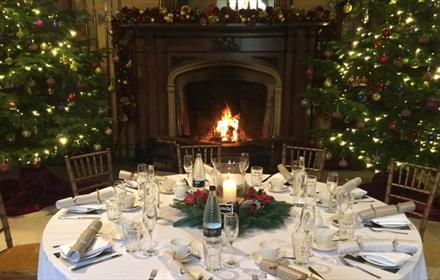 table with festive decoration, Chrismas trees, open fire