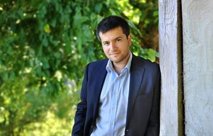 Photo of Florian Mitrea (solo pianist) wearing a navy suit in front of a leafy background.