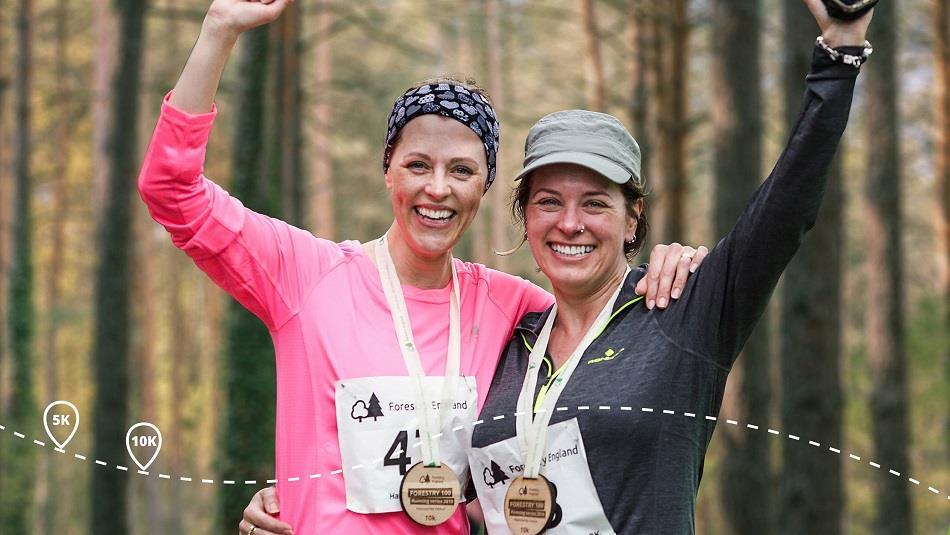 Two women taking part in run in forest.