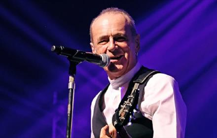 Francis Rossi on stage playing a guitar